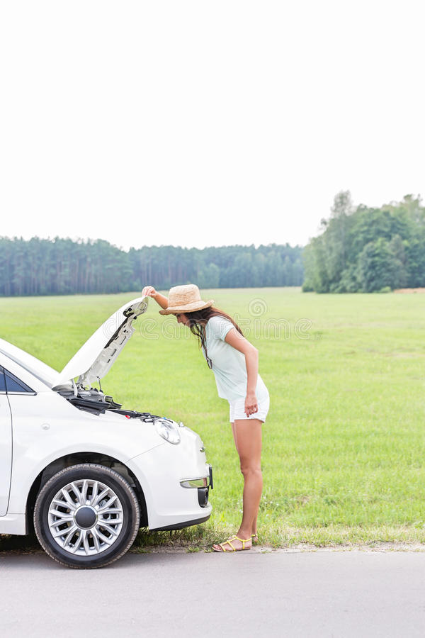 Side view of woman examining broken down car on country road stock image