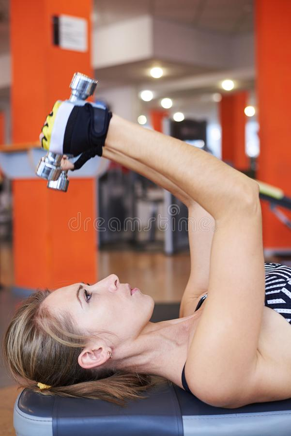 Woman lifting dumbbells while doing workout stock photos