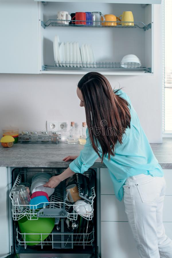 Side view of the woman pulls clean dishes from the dishwasher stock photos