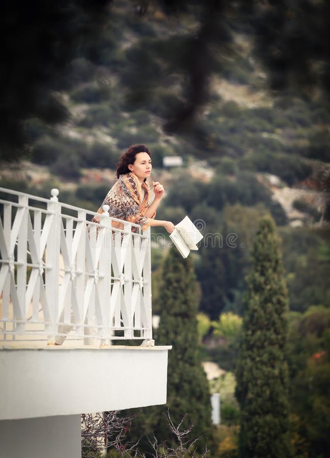 Side view of a woman reading a book in a balcony. royalty free stock image
