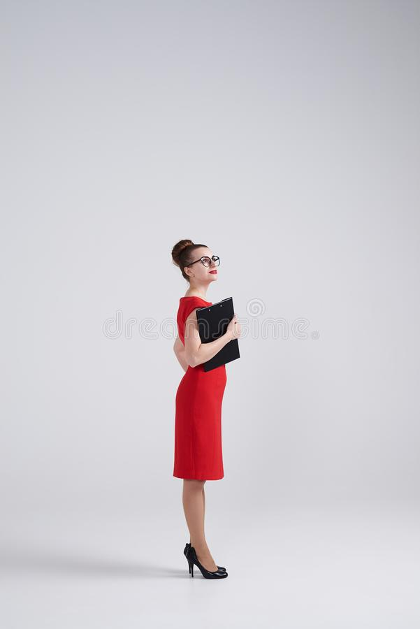 Woman in red dress and glasses looking upward at studio. Side view of woman in red dress and glasses looking upward at studio royalty free stock photos