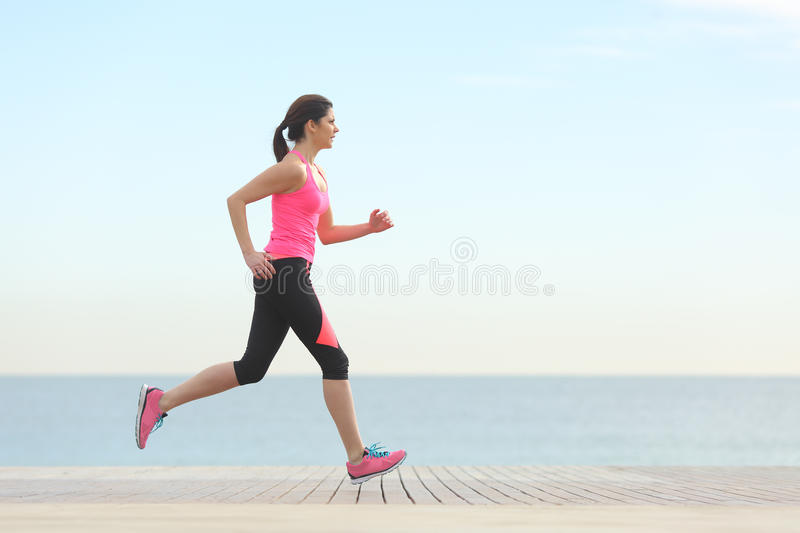 Side view of a woman running on the beach stock photography