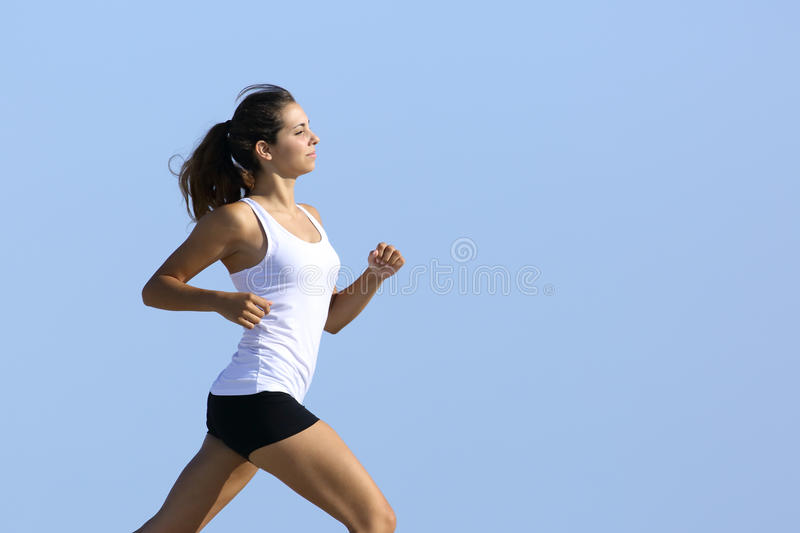 Side view of a woman running with the sky in the background stock photography