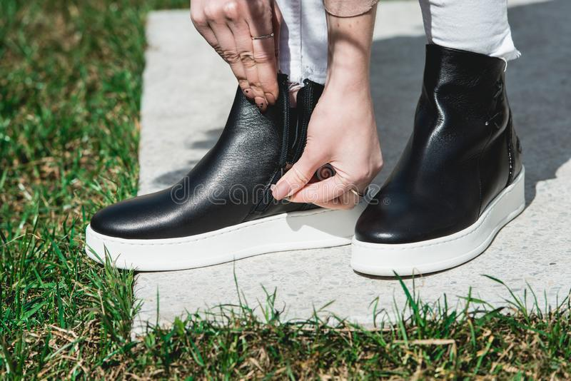 Side View Of Woman`s Black Leather Ankle Boots. Outdoor Shot Over White Stone in park royalty free stock photos