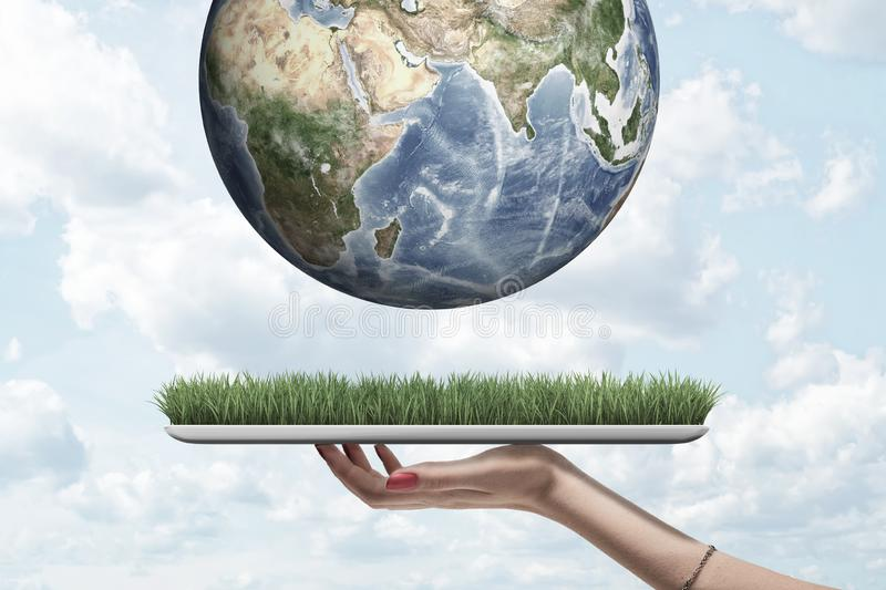 Side view of woman`s hand holding digital tablet with grass on screen and crop closeup of Earth above it in air against royalty free stock images