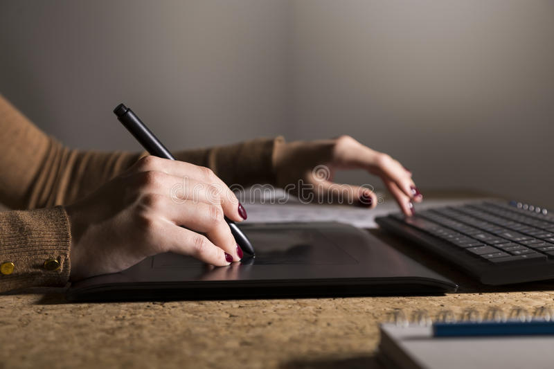 Side view of woman`s hands drawing on her pad and typing stock image