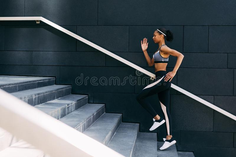 Side view of woman in sportswear running up the steps in the city royalty free stock images