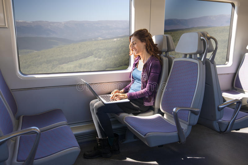Side view of woman in train typing on laptop computer stock photo