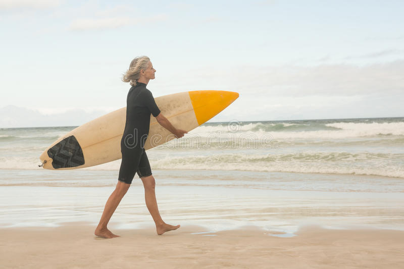 Side view of woman walking with surfboard on shore stock photo