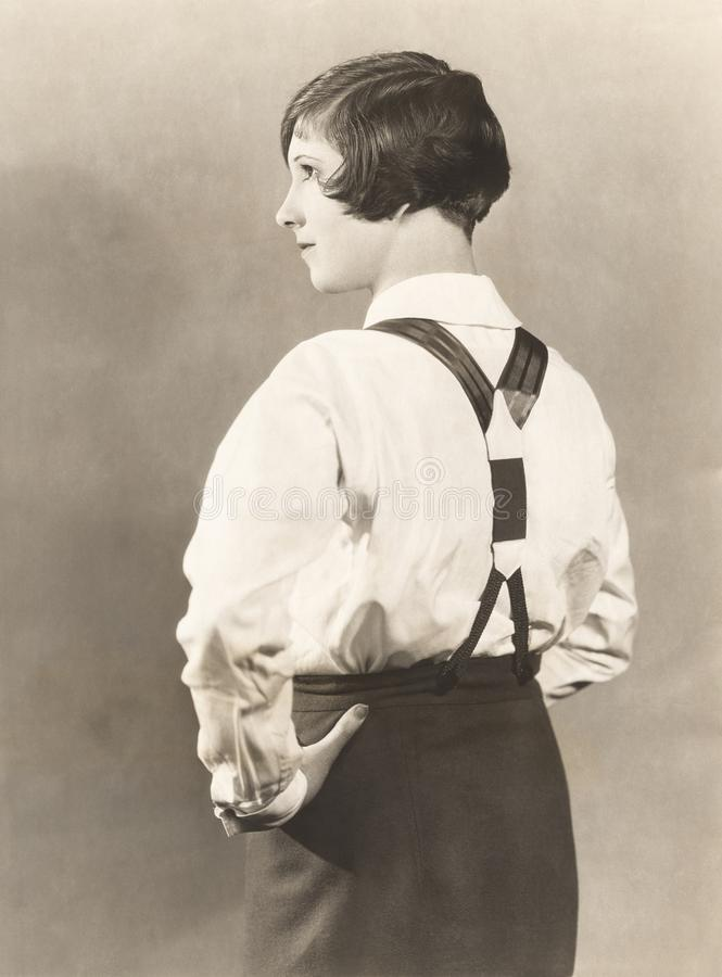 Side view of woman wearing suspenders and men's trousers, 1920s royalty free stock photos