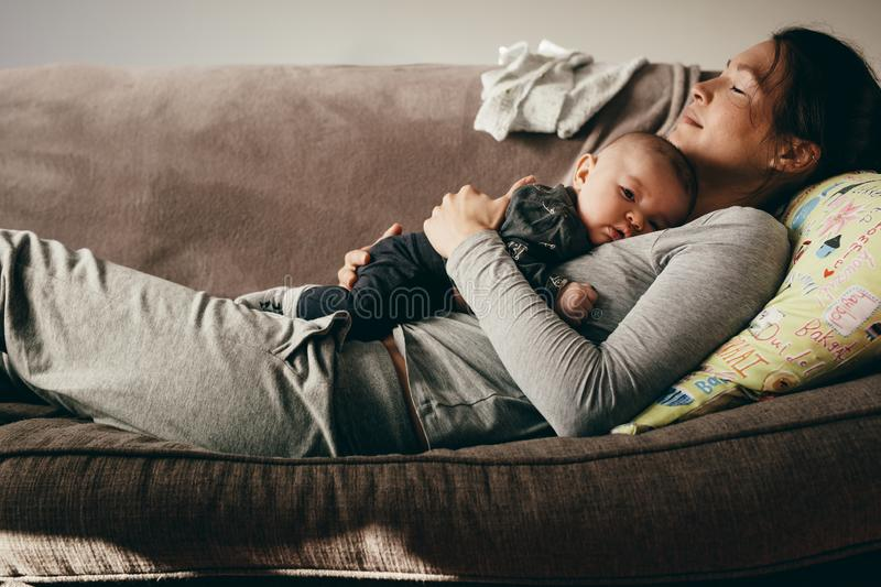 Mother sleeping on a couch with her baby on her royalty free stock photography