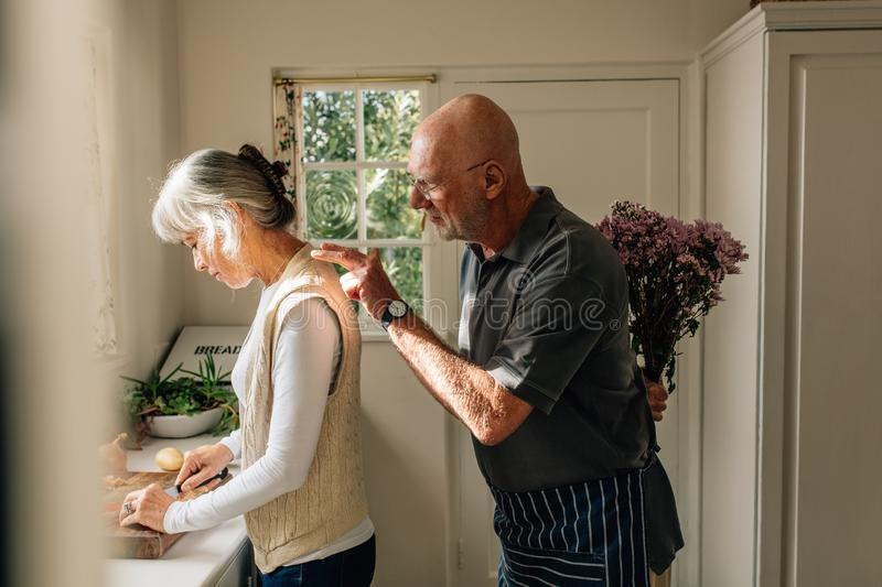 Side view of a woman working in kitchen with her husband standing behind with a bouquet of flowers. Senior man hiding a bunch of stock photography