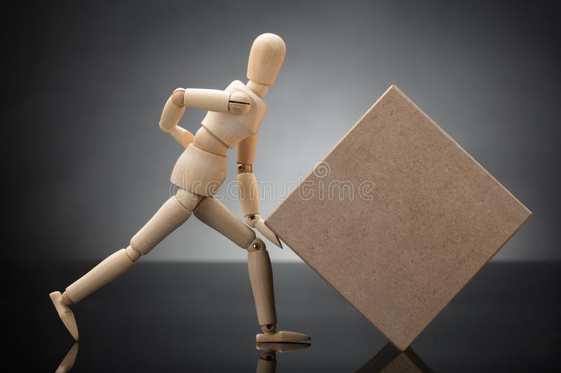 Wooden Dummy Lifting Cardboard Box Suffering From Back Pain stock images