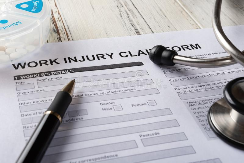 Side view work injury claim form with stethoscope and box of pills medical & insurance concept stock photo