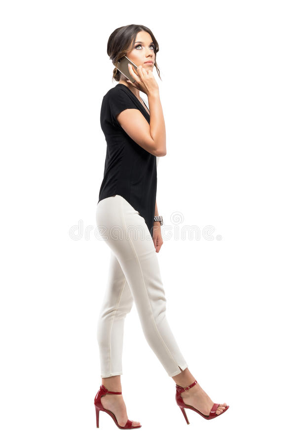 Side view of worried young business woman on the phone talking and looking up royalty free stock photography