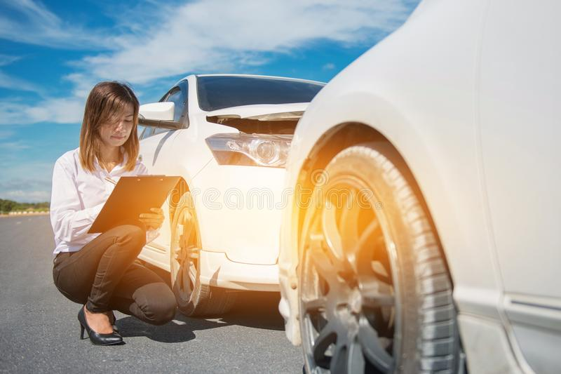 Side view of writing on clipboard while insurance agent examining car after accident.  royalty free stock photography