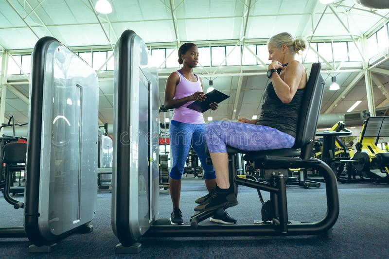 Female trainer assisting active senior woman to work out on leg curl machine stock image