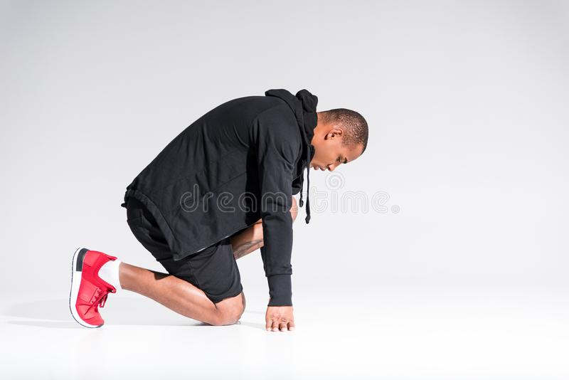 side view of young african american sportsman in hoodie kneeling stock image