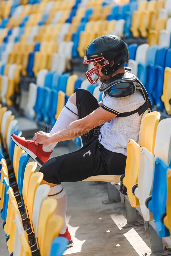 side view of young american football player sitting on tribunes at sports stadium and lacing stock photo