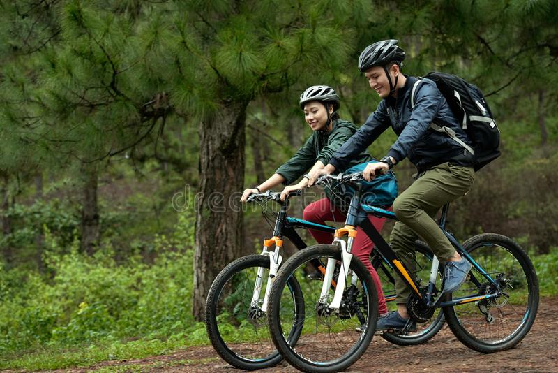 Couple cycling through forest royalty free stock photos