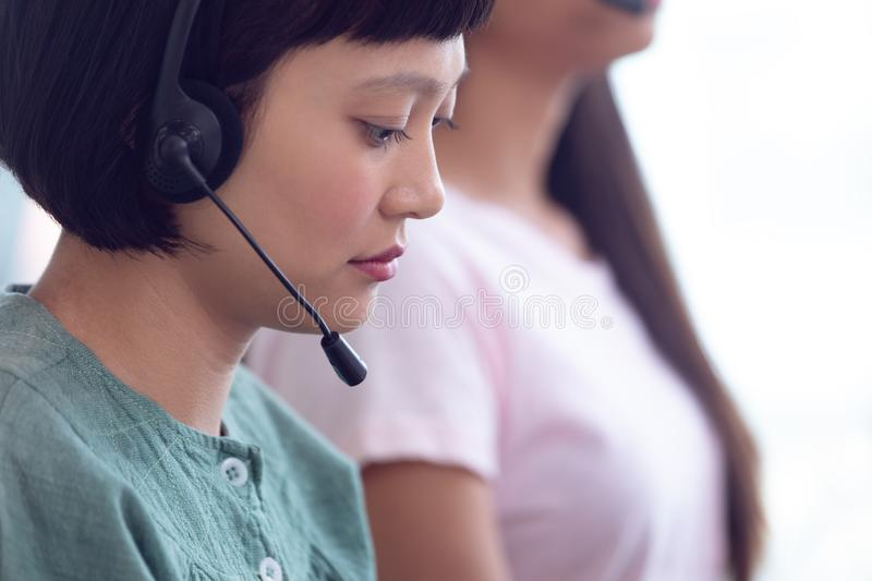 Female customer service executive working on computer in office. Side view of young Asian female customer service executive working on computer in office royalty free stock photography