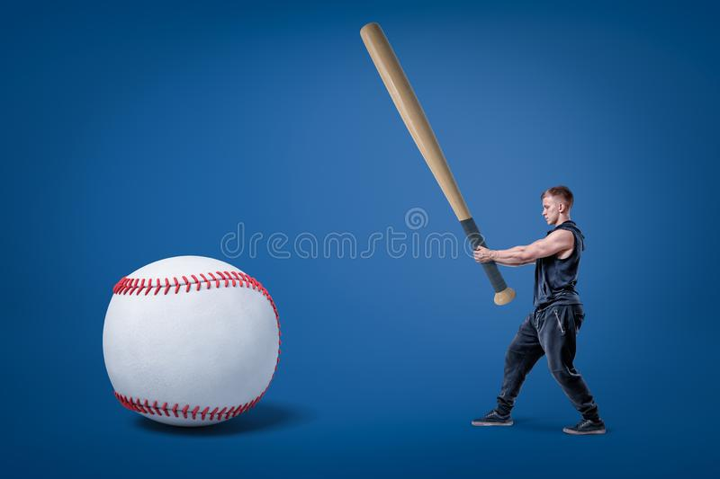 Side view of young athletic man in gym suit, holding enormous bat and ready to hit huge baseball. stock photo