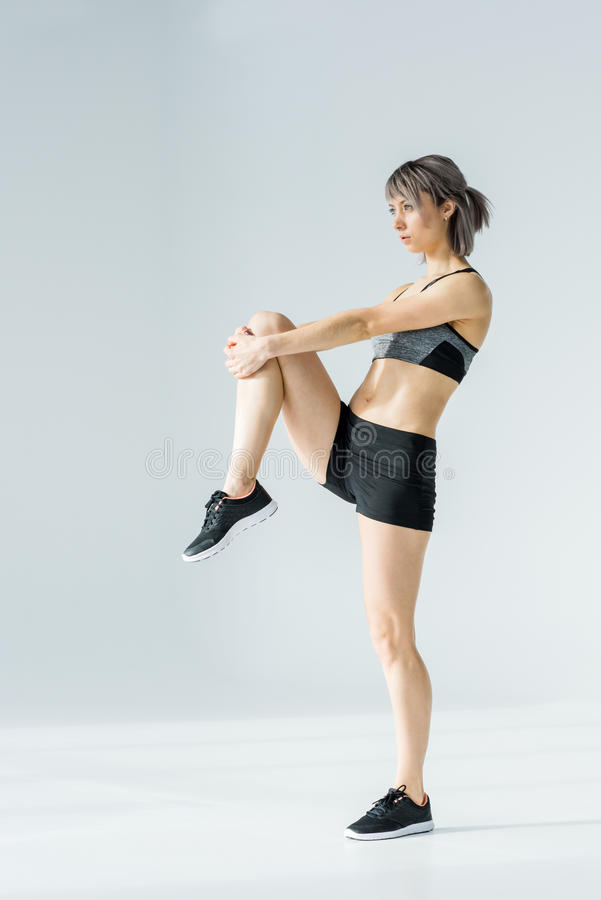 Side view of young athletic woman in sportswear exercising and looking away stock photo