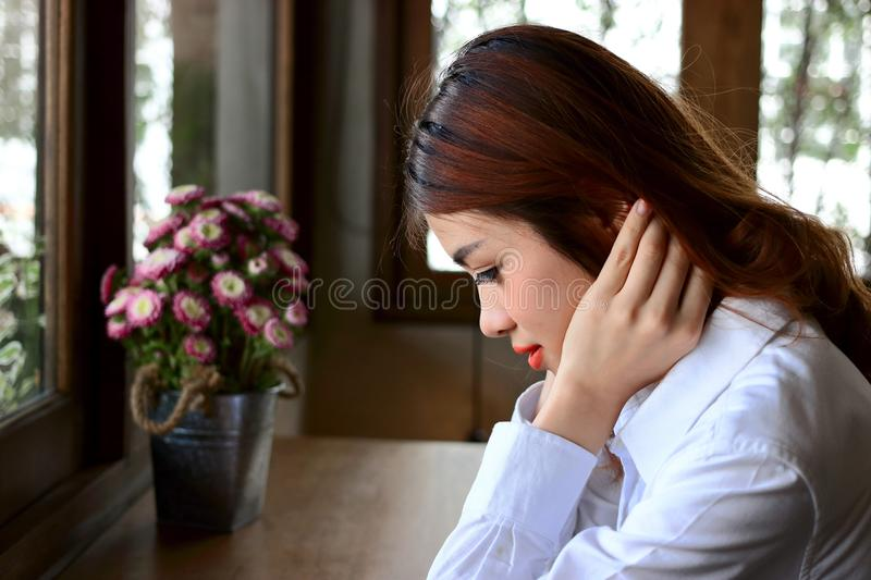 Side view of young attractive Asian business woman sitting in coffee cafe. royalty free stock photography