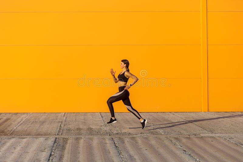 Side view of young attractive sporty woman wearing black sporwear practicing sport exercises in morning on street, start to run. With speed, running silhouette royalty free stock photos