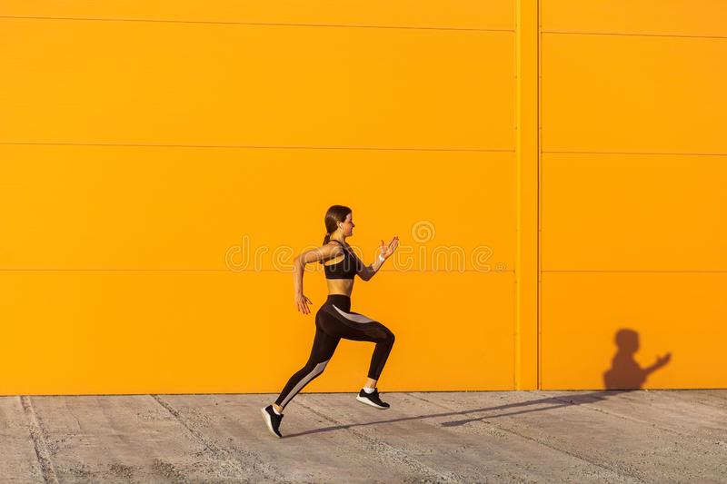 Side view of young attractive sporty woman wearing black sporwear practicing sport exercises in morning on street, start to run. With speed, running silhouette royalty free stock photo