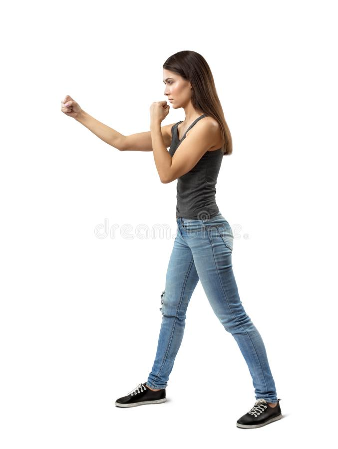 Side view of young attractive woman in gray sleeveless top and blue jeans posing with arms in figthing position isolated stock image