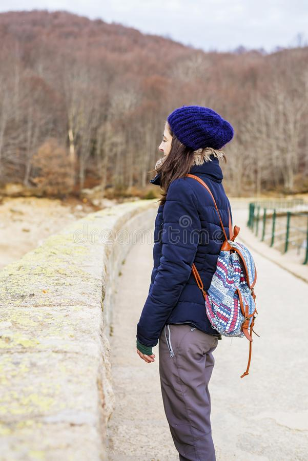 Side view of a young backpacker woman standing while looking away in the forest stock photos