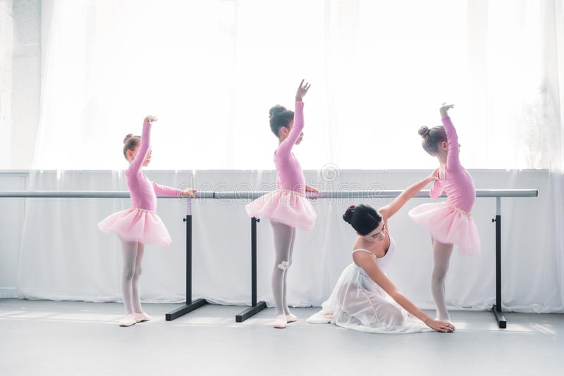 Side view of young ballet teacher exercising with kids in ballet. School royalty free stock photo