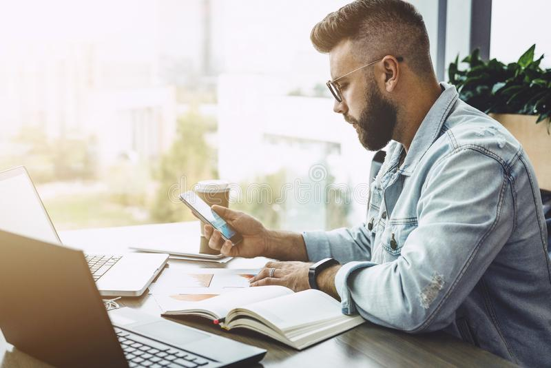 Side view. Young bearded hipster businessman working on laptop while checks information on smartphone. Adult education. royalty free stock photo