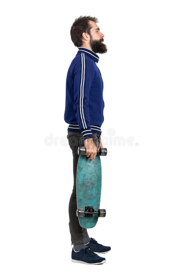 Side view of young bearded hipster in tracksuit jacket carrying skateboard. royalty free stock images