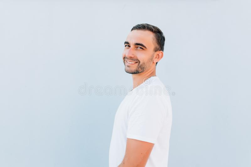 Side view of young bearded man isolated on blue background stock photo