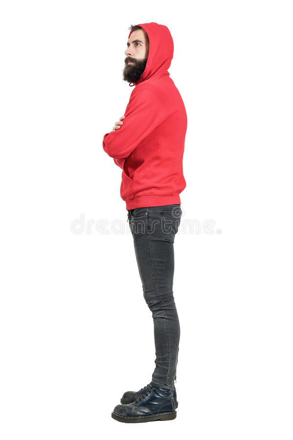 Side view of young bearded man in red hooded sweatshirt with crossed arms looking away. Full body length portrait isolated over white studio background stock images