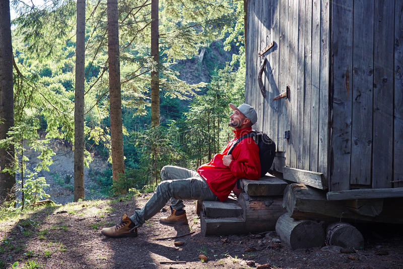 Inspired man sitting on stairs of wooden house. Side view of young bearded man sitting on stairs of wooden house in the morning royalty free stock photo