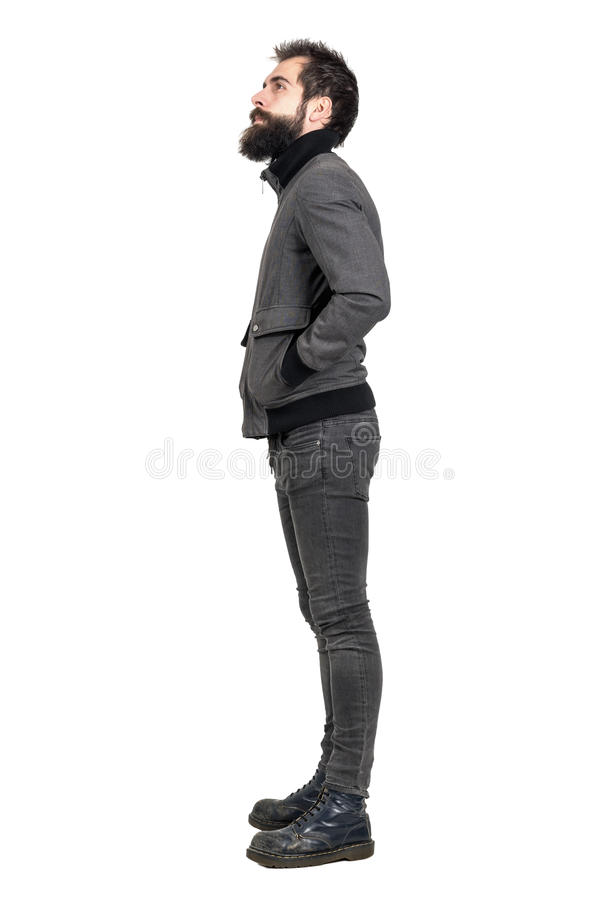 Side view of young bearded punker in old army boots looking up with hands in pockets. Full body length portrait isolated over white studio background royalty free stock images