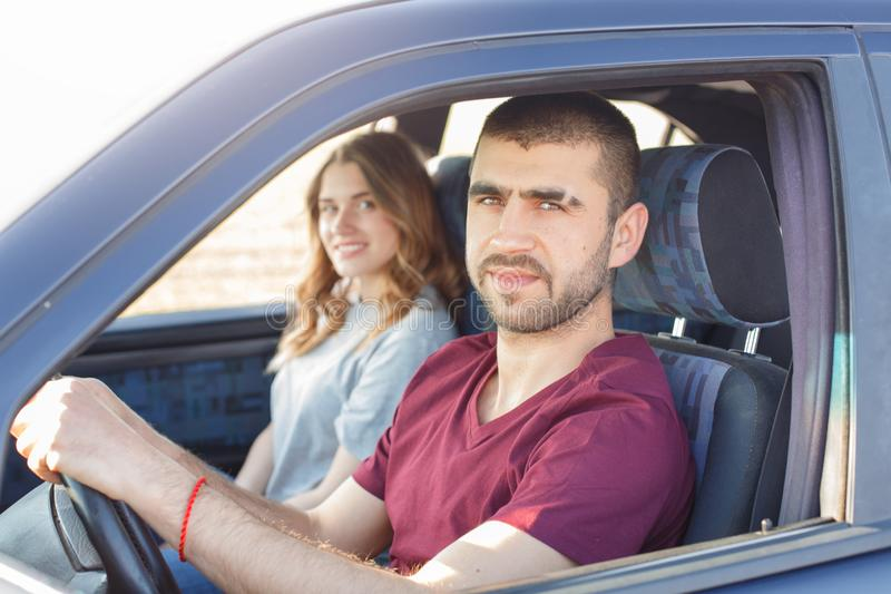 Side view of young beautiful couple has trip in car, look at camera, being in their automobile, enjoy high speed. Family cover. Destination in automobile during stock photos