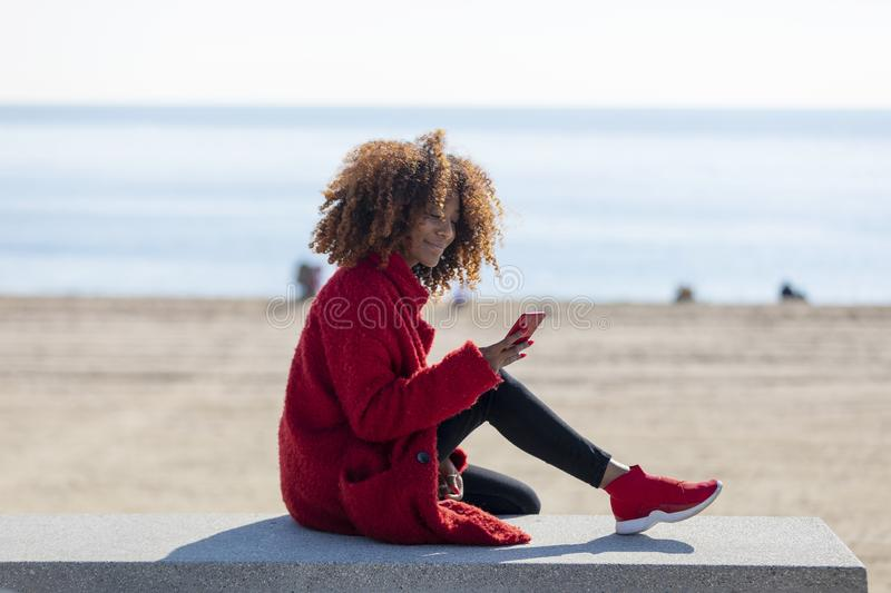 Side view of young beautiful curly african american woman sitting on a bench at beach while using a mobile phone outdoors royalty free stock photo