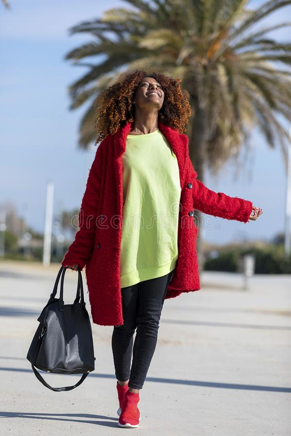 Side view of a young beautiful curly afro woman smiling and looking away while standing on city path in a sunny day royalty free stock photos