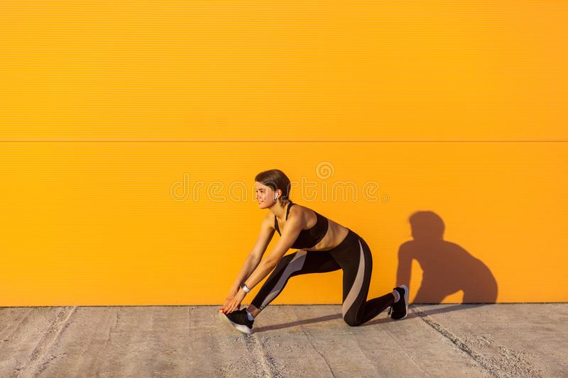 Side view of young beautiful sporty yogi female in black sportwear stretching on the street floor standing on knee, looking stock images