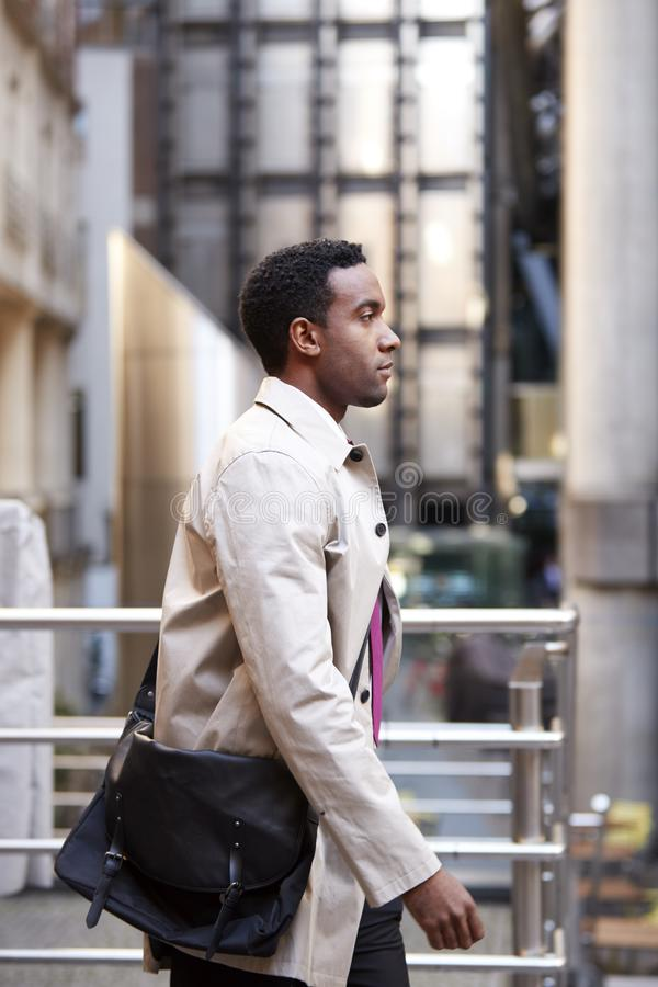 Side view of a young black businessman walking in a street in the city, London UK, close up royalty free stock photography