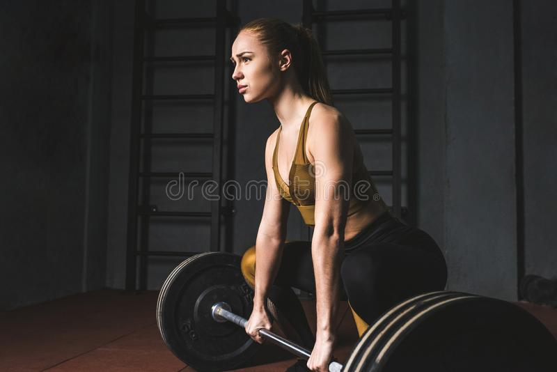 Side view of young bodybuilder preparing to raise barbell. In gym stock image