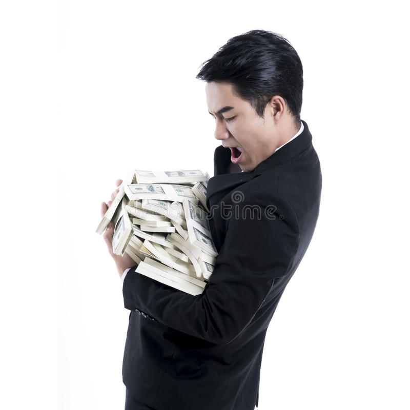 A side view of a young businessman carrying a large pile of money in his arms. royalty free stock photography