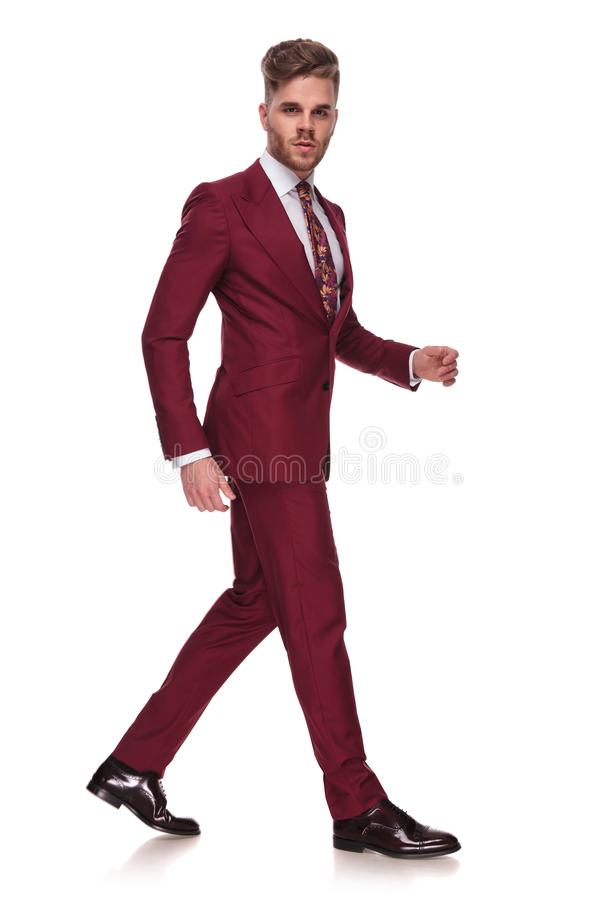 Side view of young businessman with parted lips walking. On white background while wearing a grena suit royalty free stock photos