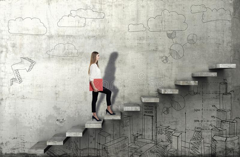 Side view of young businesswoman climbing the stairs with business sketch on concrete background. E view of young businesswoman climbing the stairs with business stock photo