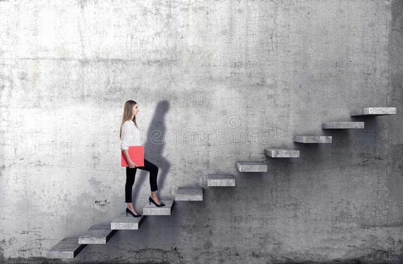 Side view of young businesswoman climbing the stairs on concrete background. Successful business concept royalty free stock photo