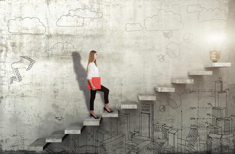Side view of young businesswoman climbing the stairs with idea lamp on concrete background. Successful business concept stock photo